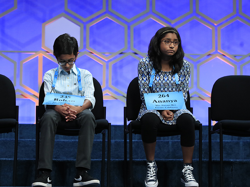 """Rohan Rajeev, 14, left, returns to his seat after misspelling the word """"marram,"""" a Scandinavian-derived word for beach grass, while Ananya Vinay, waits for her turn during the 2017 Scripps National Spelling Bee. Vinay, won by spelling """"marocain,"""" a French word for dress fabric made of ribbed crepe."""