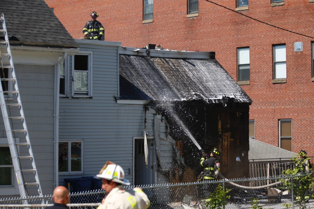 Firefighters work to extinguish a fire at a three-family apartment building on Alder Street in Portland on Tuesday.