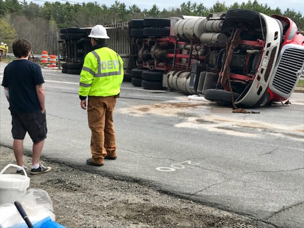 The driver of an overturned tractor-trailer, and personnel from the state Department of Environmental Protection, stand near the wreck just off the southbound exit off Interstate 295 on the Falmouth Spur on Friday afternoon. The driver, who refused to identify himself, citing company policy, appeared to have suffered only cuts on his left arm. The truck, which had Prince Edward Island tags and bore the company name Bulk Carriers, was carrying a full load of peat moss, which had to be unloaded before the truck could be righted because the weight would break the trailer.