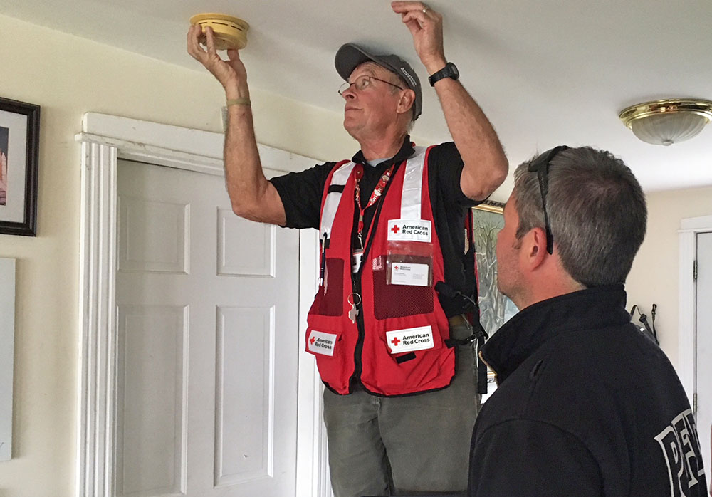 Volunteer John Cordts checks the condition of a homeowner's smoke alarm, while Brandon Farley watches. Farley is a firefighter and paramedic and vice president of Local 740 of the Portland Professional Firefighters.
