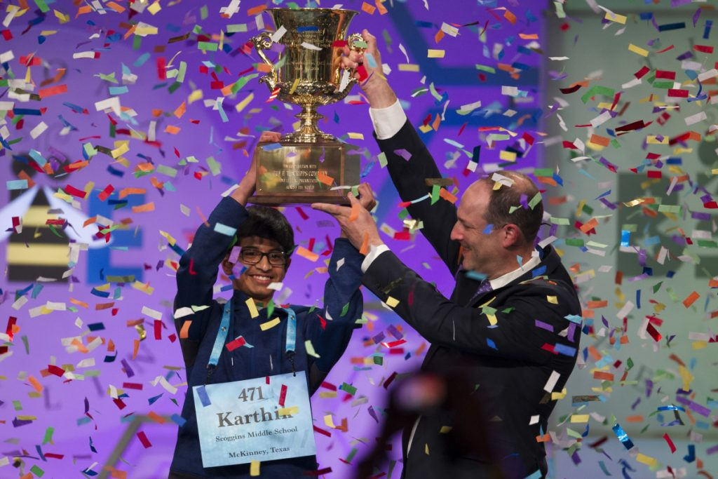 Karthik Nemmani, 14, from McKinney, Texas, is presented with the Scripps National Spelling Bee trophy by Adam Symson, president and CEO, E.W. Scripps Company.