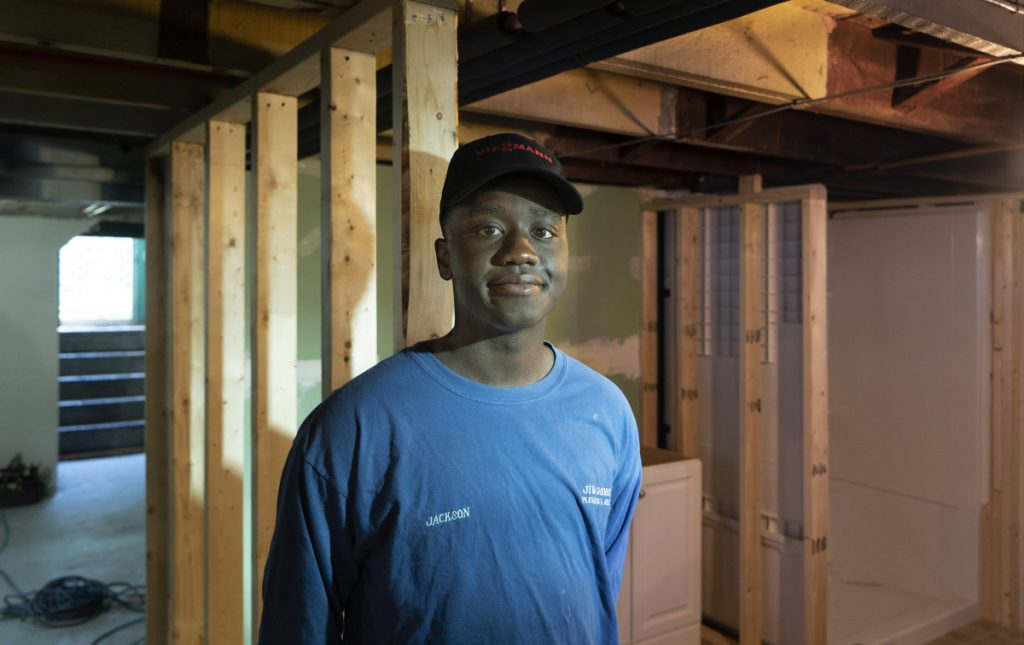 "Jackson Oloya works in the basement of a home in Biddeford, where he has an internship with a plumber. Oloya came from Uganda as a young child, and has studied to be a plumber through the Biddeford Regional Center of Technology. ""I enjoy putting things together, and I don't want to be working in an office,"" he said."
