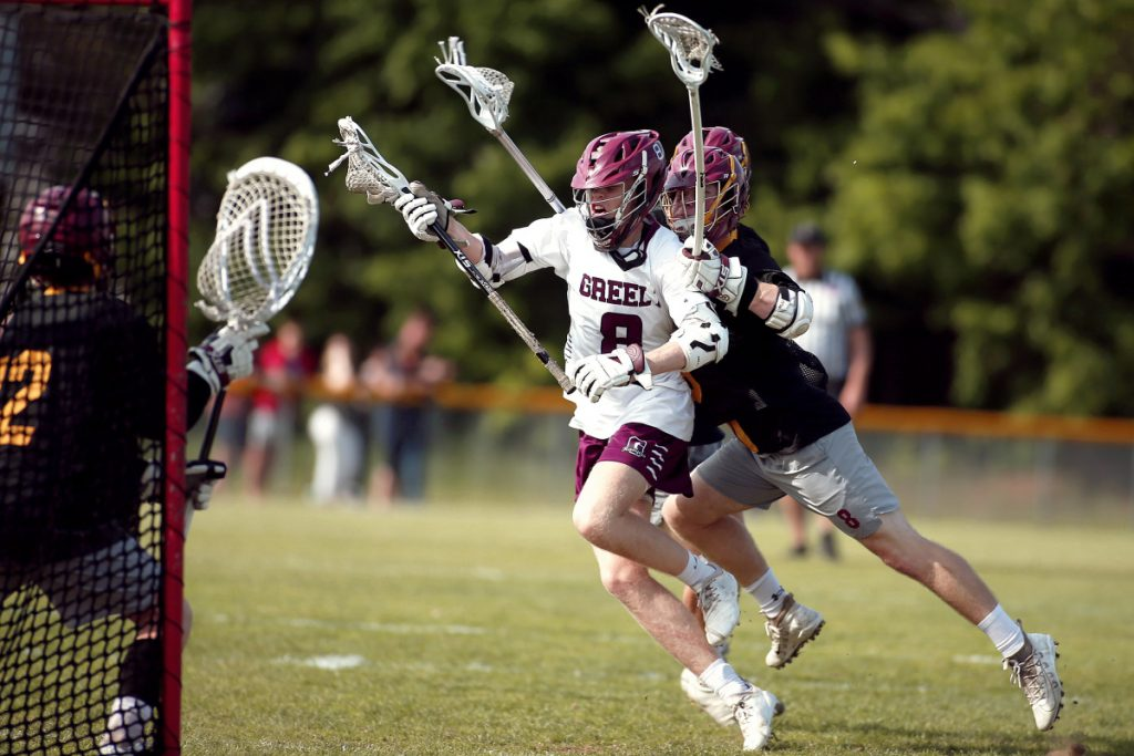 Andrew Lawrence of Greely is tripped up by Cape Elizabeth defenders Brendan Goss and Sam Loring before unloading a shot on goalkeeper Jack Dresser during their boys' lacrosse game Friday. Cape Elizabeth held on for an 11-9 victory.