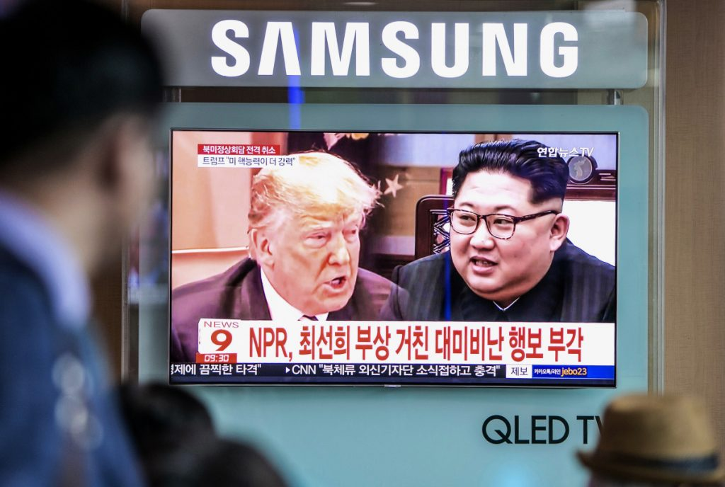 People watch a television screen broadcasting a news report featuring images of President Trump and North Korean leader Kim Jong Un in Seoul, South Korea, last month.