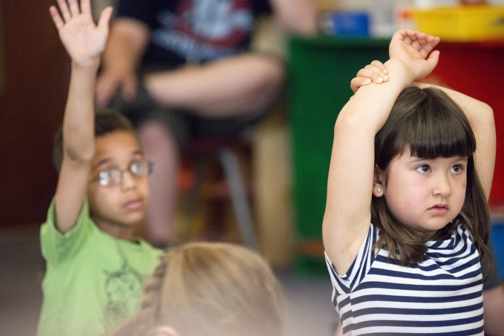 Samire Page, right, raises her hand to ask a question in Jen Morneault's first-grade class at Winslow Elementary School on May 18.