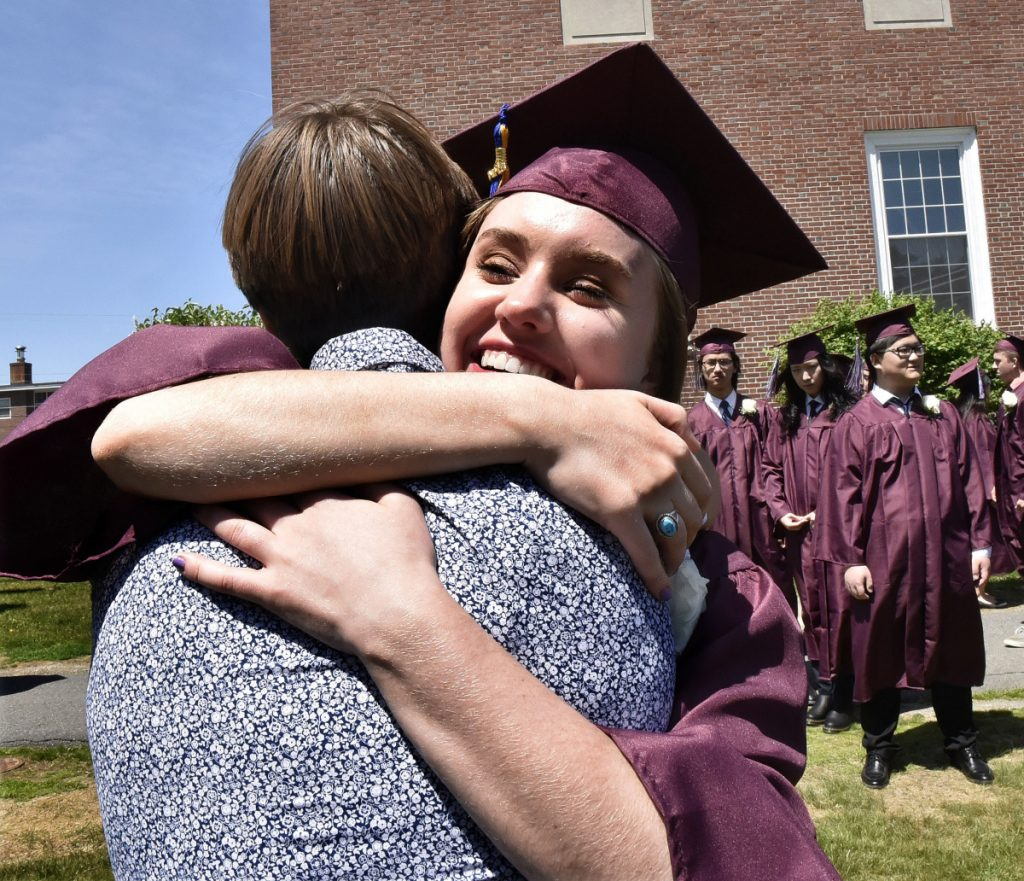 Maine Central Institute student Hannah Folan hugs friend Arjan Orr prior to commencement in Pittsfield on Sunday.