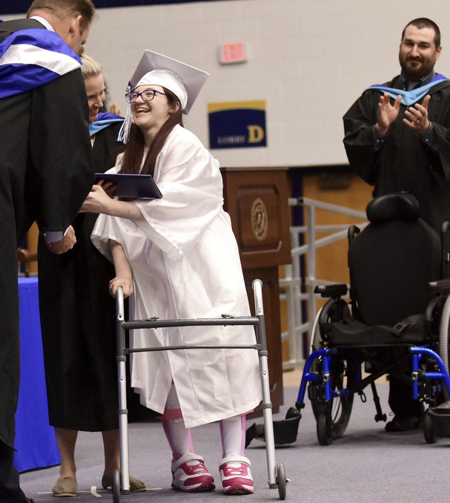 Lexi Wright leaves her wheelchair and walks across the stage to accept her diploma at Ravenna High School's graduation at Kent State University in Kent, Ohio.