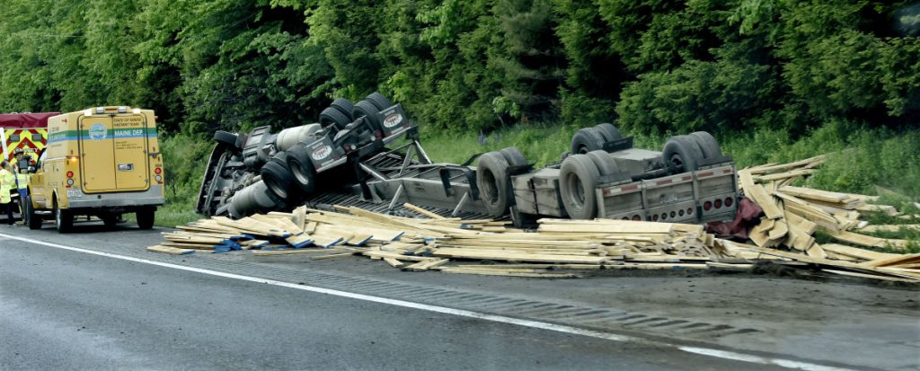 First responders wait for police to reconstruct the tractor-trailer rollover Monday on the southbound side of Interstate 95 in Sidney. The truck was loaded with lumber.