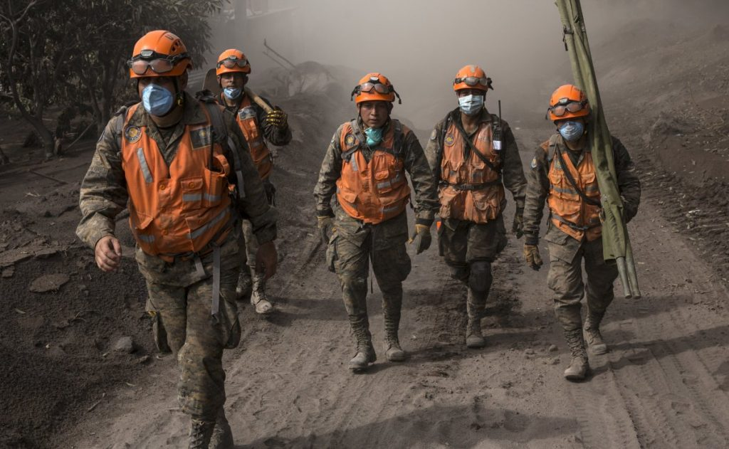 Rescue workers walk near the Volcan de Fuego in El Rodeo, Guatemala, Wednesday. Nearly 200 people are still missing.