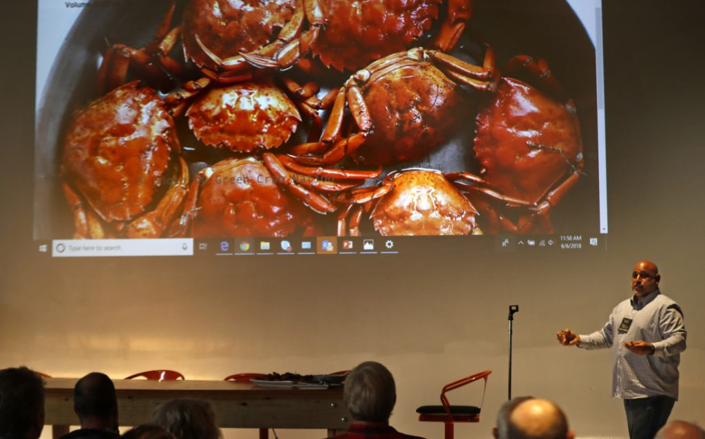 Jamie Bassett, a crabber from Chatham, Mass., presents culinary uses for green crabs at a conference in Portland on Wednesday. The crabs will be harvested if there's a market, potentially reducing their predation of shellfish.