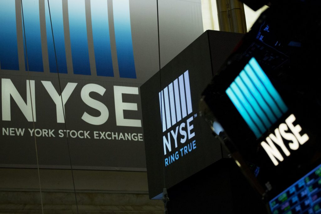 Signs for the New York Stock Exchange hang above the trading floor in May. Banks and bond yields climbed Wednesday, lifting the market to its fourth gain in a row, Associated Press/Mark Lennihan