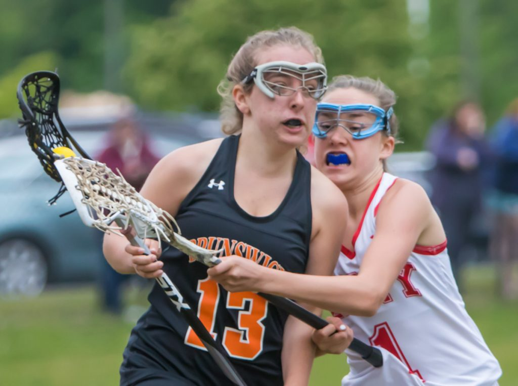 Cony defender Sierra Clark, right, tries to knock the ball away from Brunswick's Lila Solberg during a Class B lacrosse playoff game Wednesday in Augusta. Brunswick won, 9-7.