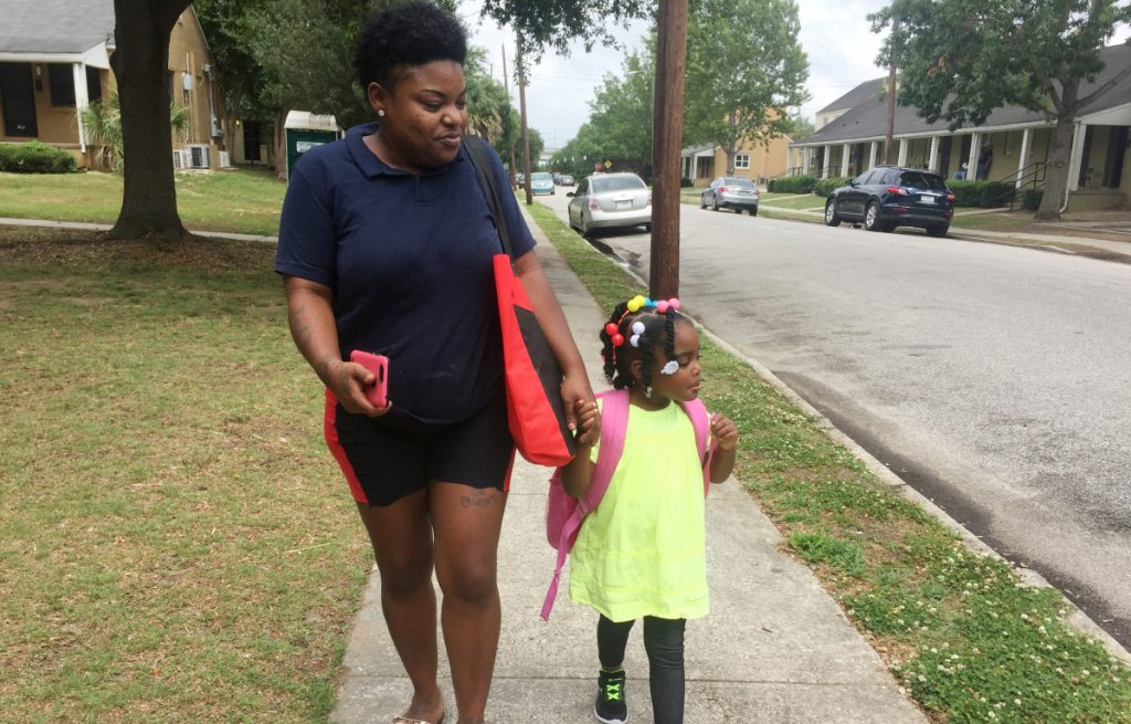"Shannon Brown, 29, with daughter, Sai-Mya, 4, in Charleston, S.C.  Brown lives in public housing and could face a steep rent increase. Housing and Urban Development Secretary Ben Carson, left, says the rent increase ""is our attempt to give poor people a way out of poverty."""