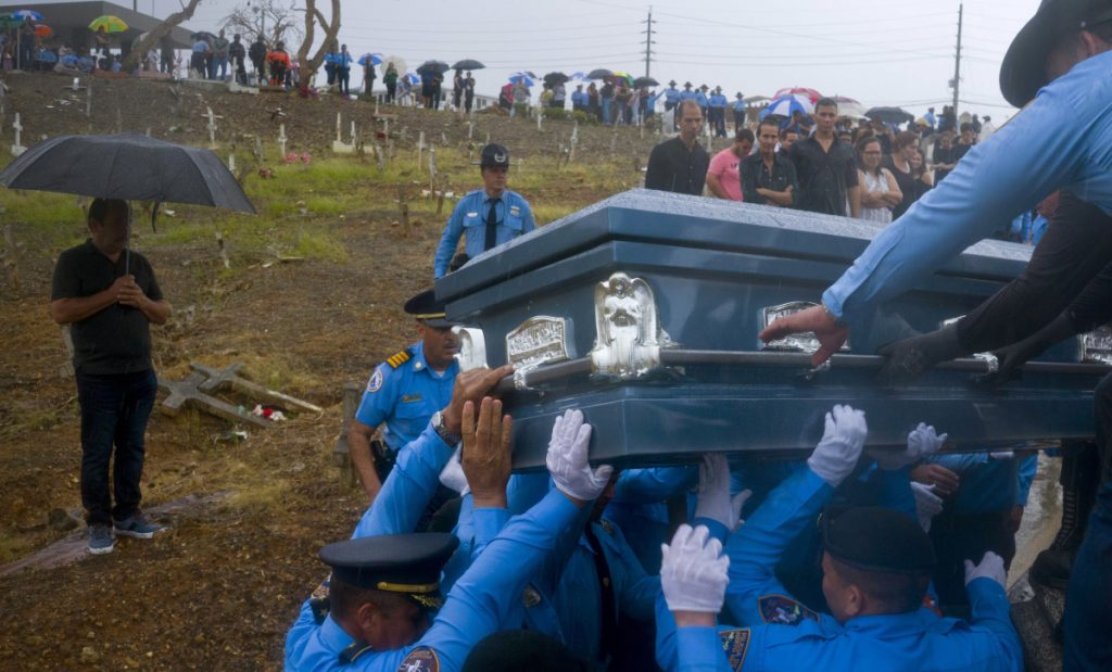 Police in Aguada, Puerto Rico, last Sept. 29 lift the coffin of officer Luis Angel Gonzalez Lorenzo, killed while trying to drive across a river during Hurricane Maria. The storm's toll reflects neglect and mismanagement.