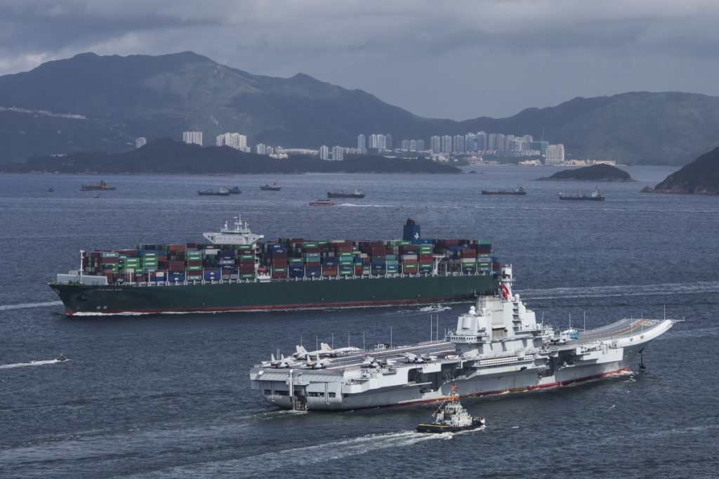 The People's Liberation Army Liaoning aircraft carrier, bottom, sails past a container ship in Hong Kong on July 7, 2017.