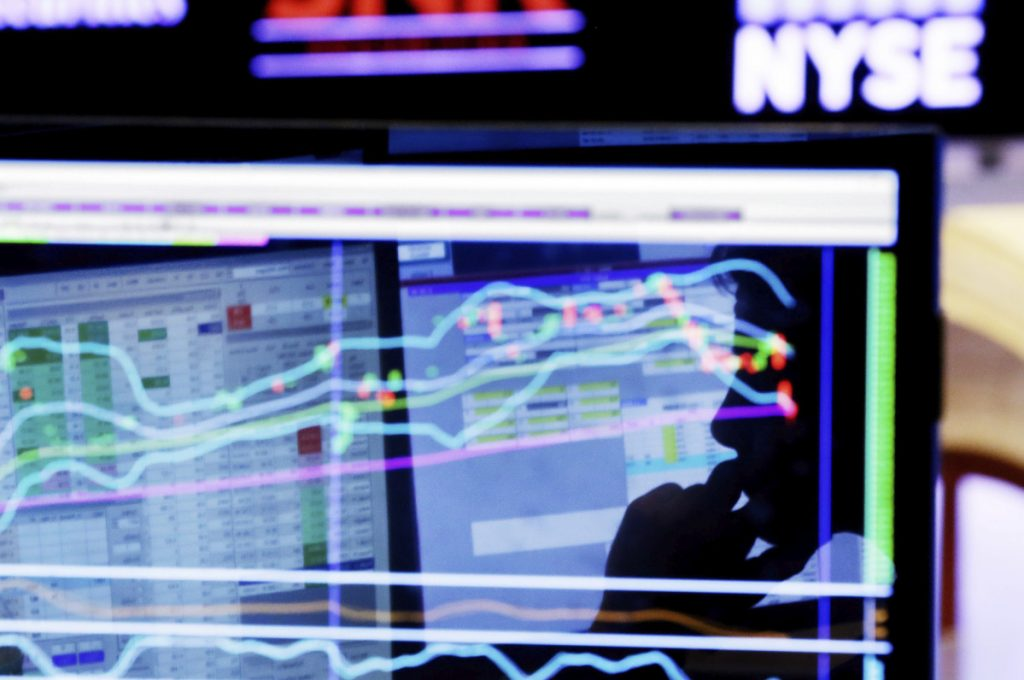 Specialist Anthony Rinaldi is silhouetted on a screen at his post on the floor of the New York Stock Exchange in this 2016 photo. Fears of a global trade war have given a boost to some of the biggest companies in the market as well as the smallest, but they've squeezed almost everything in the middle.