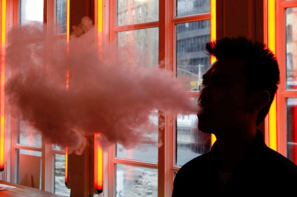 A customer exhales vapor from an e-cigarette at a store in New York. Many e-cigarette and vaporizer sellers have started offering scholarships as a way to get brands listed on university websites and to get students to write essays about vaping.