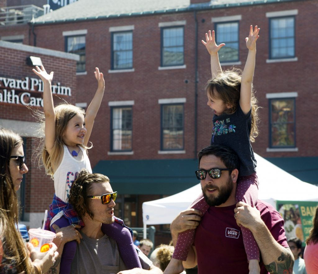 As Steven McCann of Bardstown, Ky., left, and his friend Joe Hughes of Ocean Park chat, their daughters Pearl McCann, 5, left, and Nixon Hughes, 6, listen to the music during the Old Port Festival in Portland on Sunday.