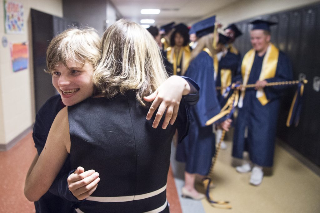 Leah Stinson hugs her personal ed tech, Alison Woodcock, with the 2018 Mt. Blue Senior High School graduating class in the hallway before commencement ceremonies at Mt. Blue High School in Farmington on Sunday.