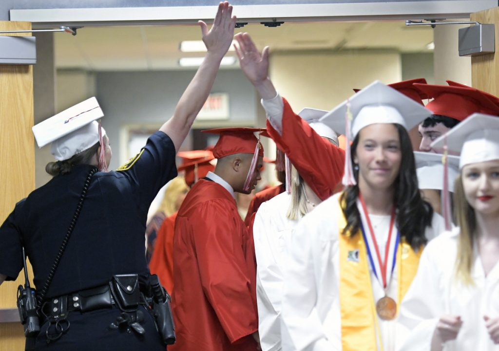 Augusta police Officer Carly Wiggin high-fives graduates of Cony High School on Sunday before graduation ceremonies at the Augusta Civic Center.