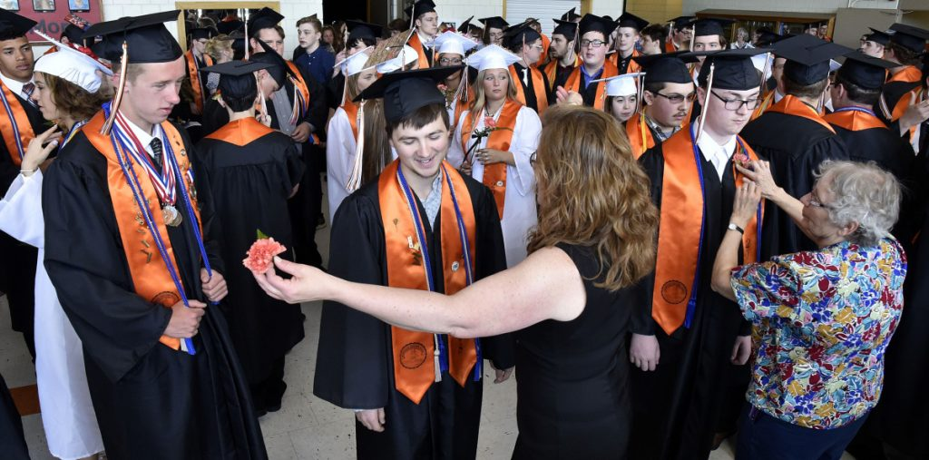 Skowhegan Area High School senior Jackman Hodges, center, gets his corsage and a hug from teacher Darcy Fitzmaurice as Eleanor McClay also pins corsages on students  prior to commencement exercises at the school Sunday.
