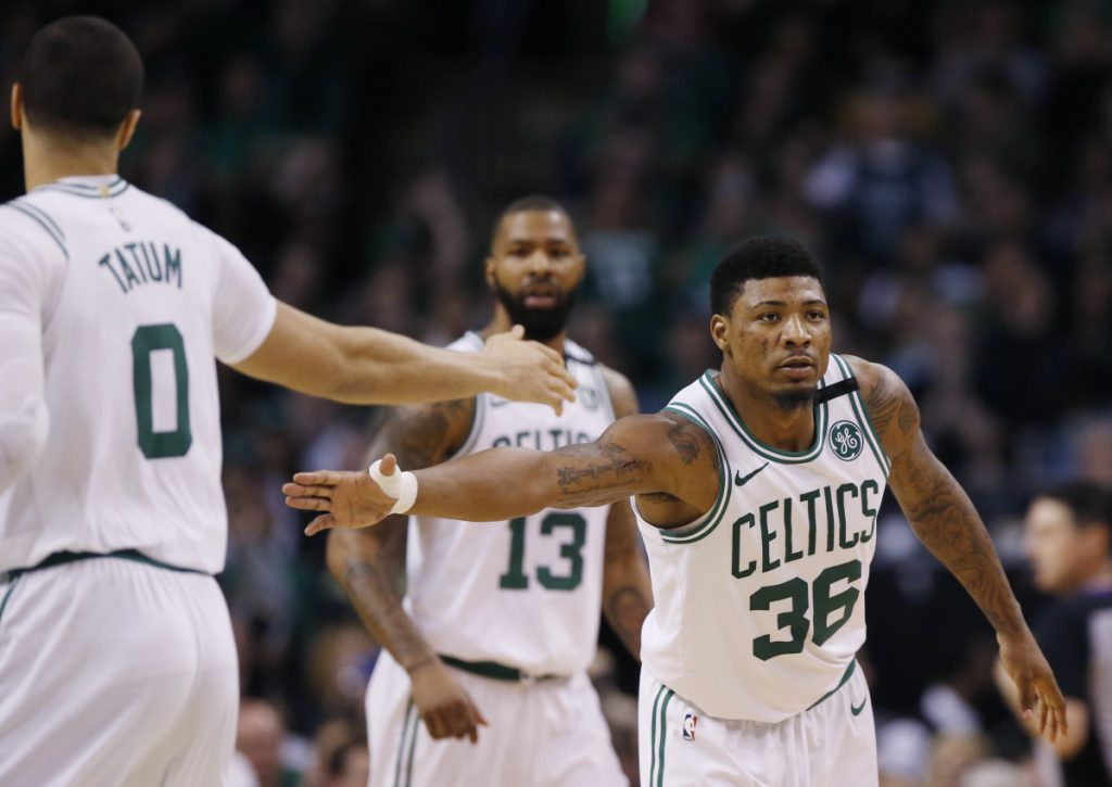 Boston Celtics guard Marcus Smart (36) reaches to slap hands with forward Jayson Tatum (0) during the second half of Game 1 of the NBA basketball Eastern Conference Finals against the Cleveland Cavaliers, Sunday, May 13, 2018, in Boston. (AP Photo/Michael Dwyer)