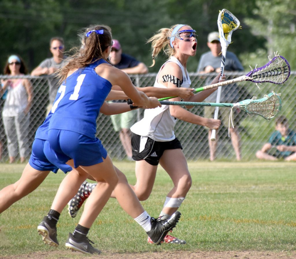 Caroline Gastonguay sets up the offense for St. Dom's against the defense of Erskine Academy's Olivia Kunesh, front, and Morgan Edmond during a Class C girls' lacrosse semifinal Tuesday.