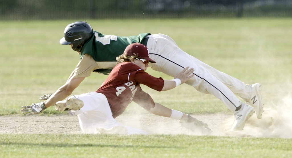 Rod Bean of Oxford Hills dives over Bangor infielder Zach Ireland but is tagged out on a steal attempt in the Class A North baseball final Tuesday.