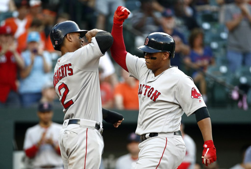 Boston's Xander Bogaerts, left, greets Rafael Devers at home plate after scoring on Devers' two-run home run during the second inning of Tuesday's game against the Orioles in Baltimore.