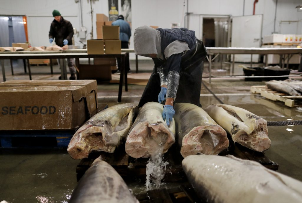 A fishmonger rinses swordfish carcasses just pulled from their shipping containers at the New Fulton Fish Market in New York on Jan. 8. The U.S. seafood industry is worth $17 billion a year, more than 90 percent of which is made up of imports. Experts say one in five fish is caught illegally worldwide.