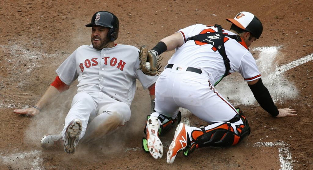Boston's J.D. Martinez slides past Orioles catcher Austin Wynns for a run on Eduardo Nunez's RBI single in the fifth inning Wednesday in Baltimore. The Red Sox finished their sweep with a 5-1 win.