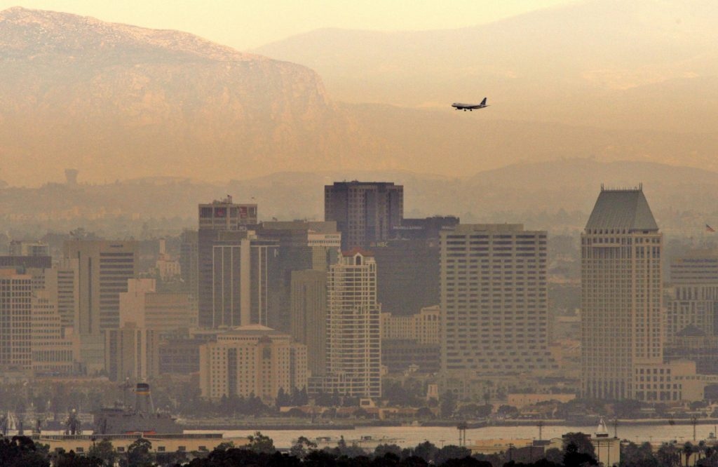 **CHANGES CITY IN MEDADATA**A heavy layer of smoke and ash from wildfires hangs over the downtown San Diego skyline as an airplane makes its approach to Lindbergh Field Saturday, Oct. 27, 2007. Pollution control authorities across Southern California warned that smoke and ash are making the air dangerous. People with heart or respiratory disease, the elderly and children in those areas were urged to remain indoors.  (AP Photo/Denis Poroy)