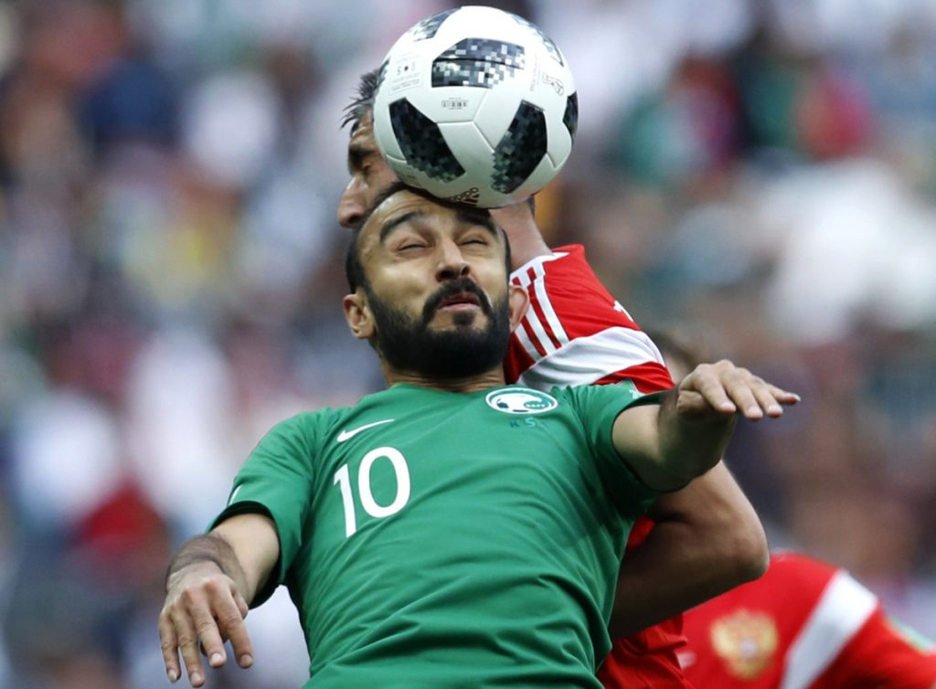Mohammed Alsahlawi, foreground, of Saudi Arabia jumps for the ball Thursday with Alexander Samedov of Russia during the group A game at Moscow that opened the World Cup.