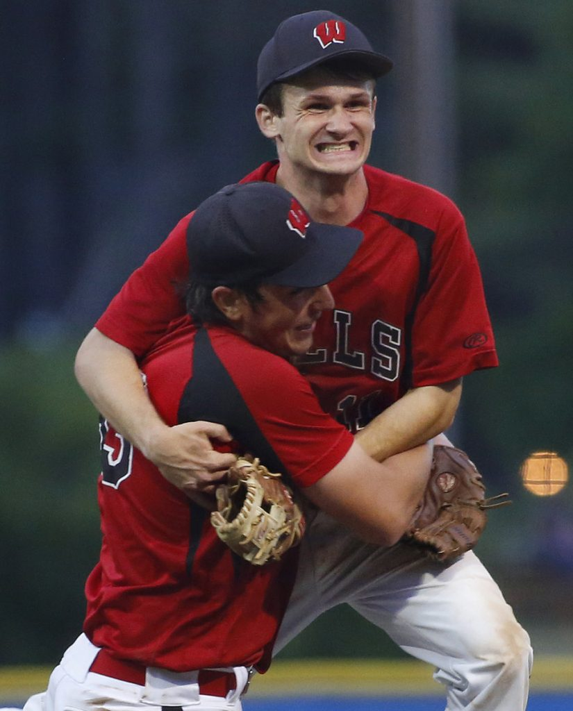 Wells pitcher Cam Cousins, front, and shortstop Liam Bell celebrate after an 8-3 win over Greely in the Class B South baseball final Wednesday night. The Warriors face Brewer in the state championship game on Saturday.