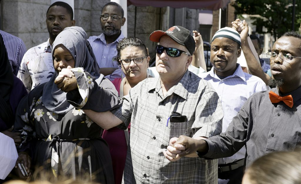 Jim Thompson holds hands with Fowsia Musse, left, and Abdi Abdalla during a gathering in Lewiston Sunday aimed at defusing ethnic tensions. Thompson is the uncle of Donald Giusti, who died from injuries he received in a brawl Tuesday.