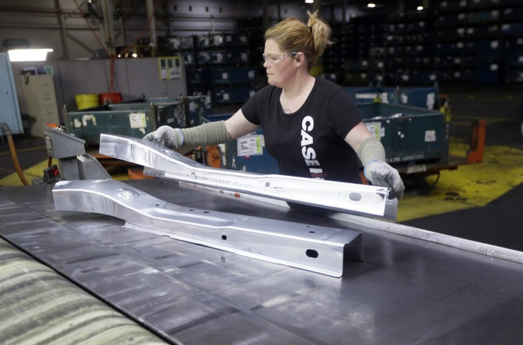 United Auto Workers line worker Crystal McIntyre unloads parts from a stamping machine at the General Motors Pontiac Metal Center in Pontiac, Mich.