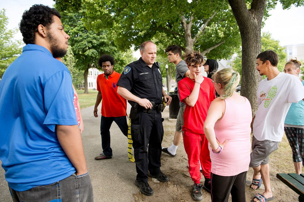 Lewiston police Officer Tom Murphy talks with people on June 13 about a brawl in Kennedy Park the previous night. Donald Giusti, 38, died Friday of injuries from the fight.