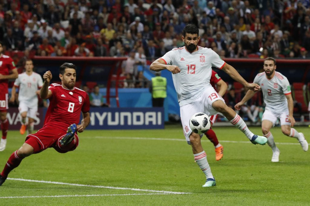 Spain's Diego Costa, right, shoots as Iran's Morteza Pouraliganji tries to block during the group B match between Iran and Spain at the World Cup on Wednesday. Spain won, 1-0.