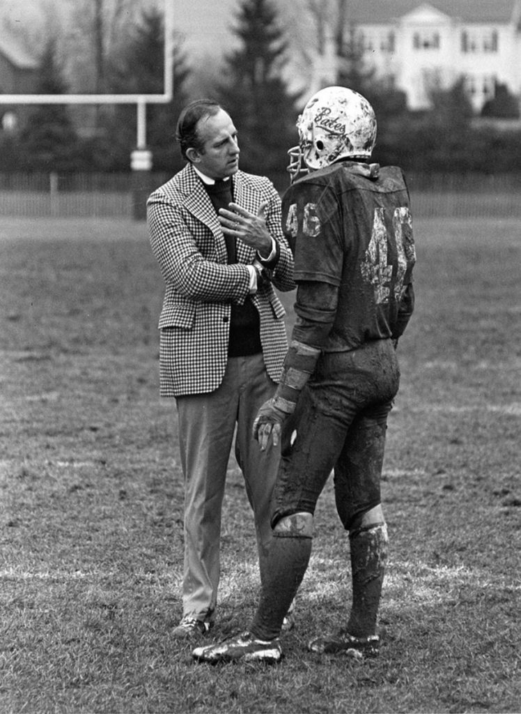 Web Harrison '63 talks with one of his Bates football players on Garcelon Field, circa 1982.