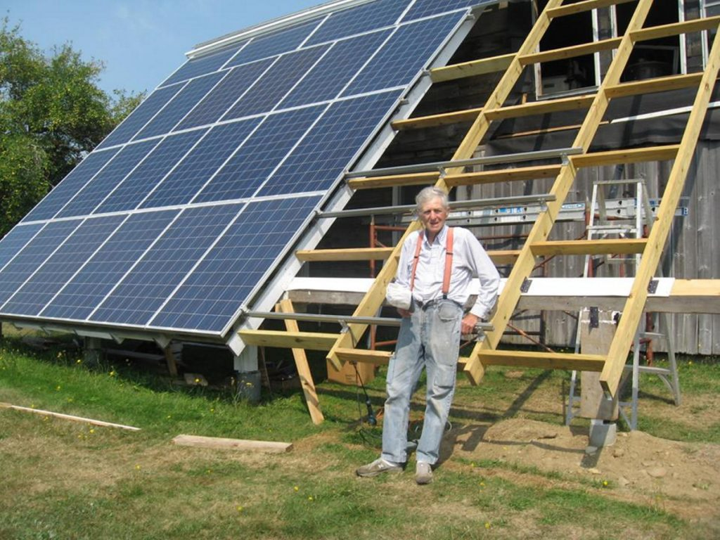 "The humble Farmer finishes up the rack for his last eight solar panels. He now has 30 of them; his monthly electric bill is about $10 ""for the convenience of being hooked to the grid."""