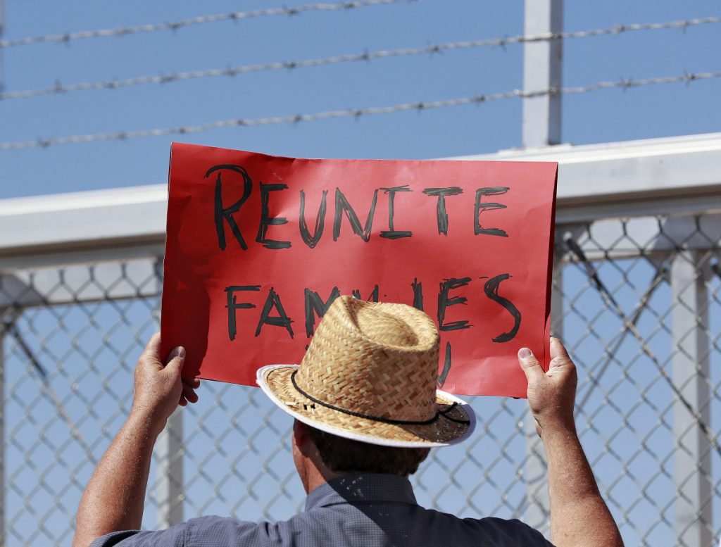 A protester holds a sign Thursday at the port of entry in Fabens, Texas, where separated families reside in tent shelters. A reader is outraged that tax dollars are funding this appalling program.