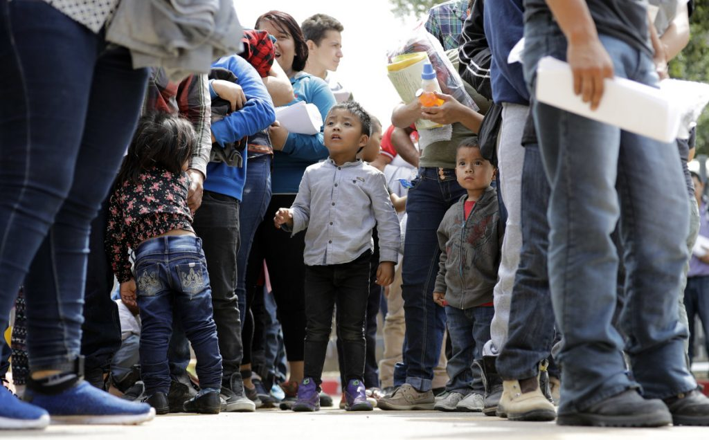 Immigrant families line up to enter the central bus station after they were processed and released by U.S. Customs and Border Protection on Sunday in McAllen, Texas. The Department of Homeland Security and the Department of Health and Human Services said 522 children have already been returned to their parents.
