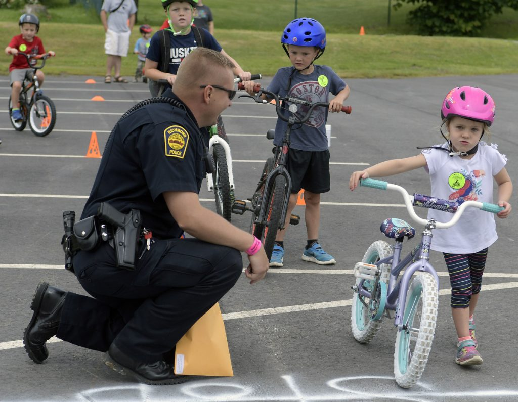Katie Emmons, 4, walks her bike through a stop sign Sunday under the supervision of Richmond police Officer Will Towle during the annual bicycle rodeo for young riders in the community.