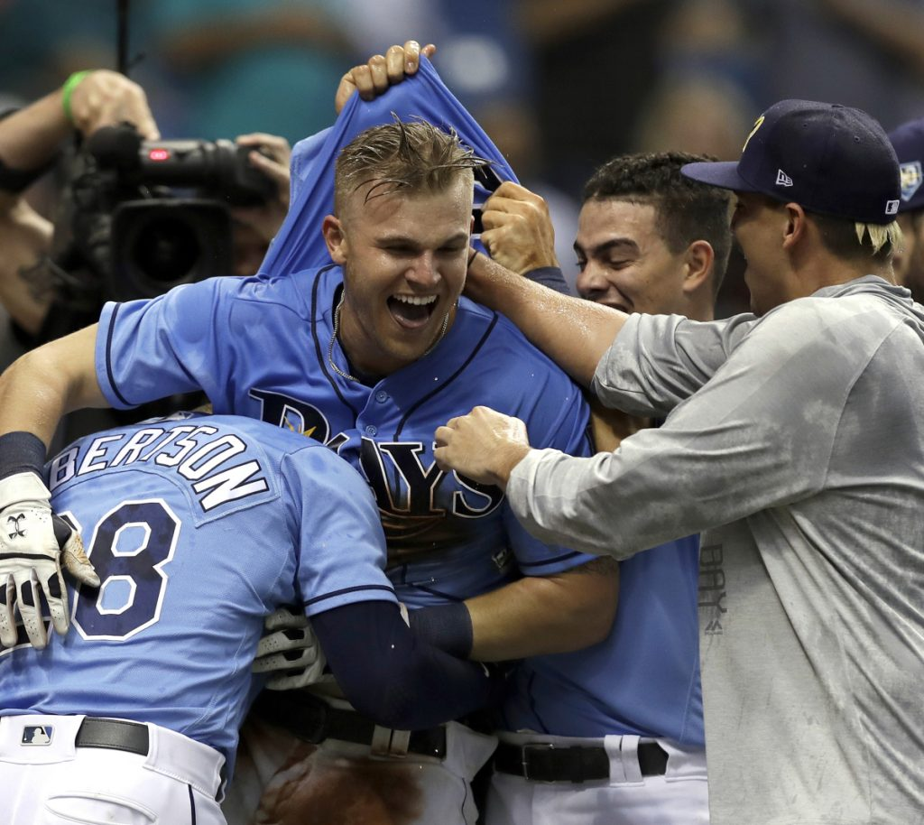 Jake Bauers of the Tampa Bay Rays, center, celebrates with teammates Sunday after hitting the 12th-inning homer that beat the New York Yankees.