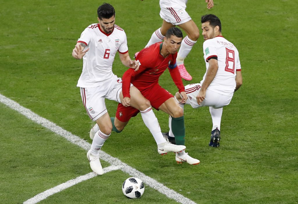 Portugal's Cristiano Ronaldo, bottom, is fouled by Iran's Saeid Ezatolahi during their Group B match against Portugal on Monday at the World Cup at the Mordovia Arena in Saransk, Russia.