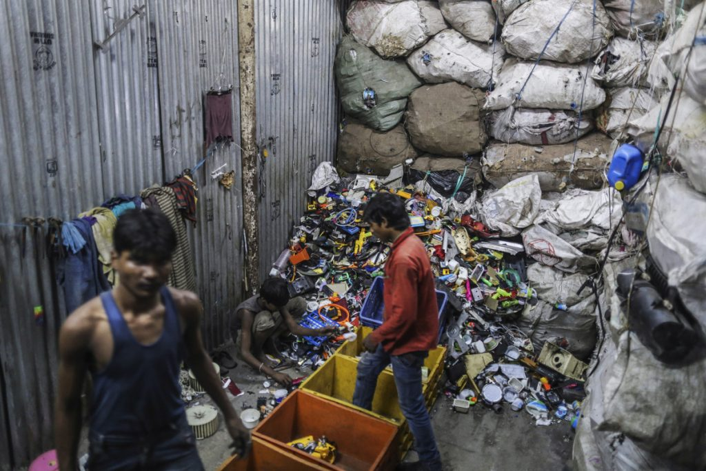 Workers sort through plastic waste for recycling in a slum area of Mumbai, India. The city is criminalizing plastic-bag use with fines – and jail for repeat offenders.