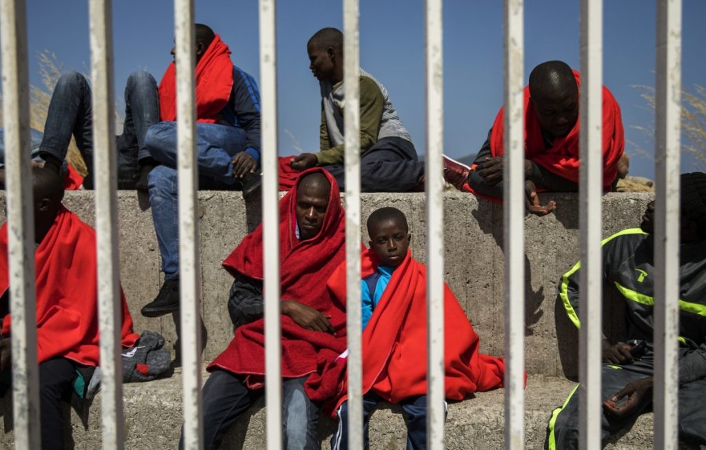 Migrants rest at the port of Algeciras, southern Spain, as they wait to be transported to a police station after being rescued in the Strait of Gibraltar Tuesday.
