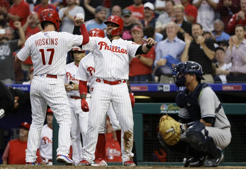 Philadelphia's Rhys Hoskins, left, and Jorge Alfaro, center, celebrate next to New York Yankees catcher Kyle Higashioka after Hoskins hit a three-run homer in the second inning Wednesday night. The Phillies shut out the visiting Yankees, 3-0.