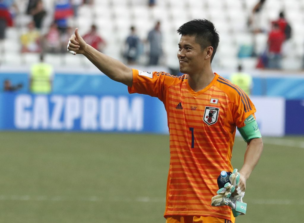 Japan goalkeeper Eiji Kawashima celebrates after his team advanced to the knockout phase of the World Cup despite its 1-0 loss Thursday against Poland.