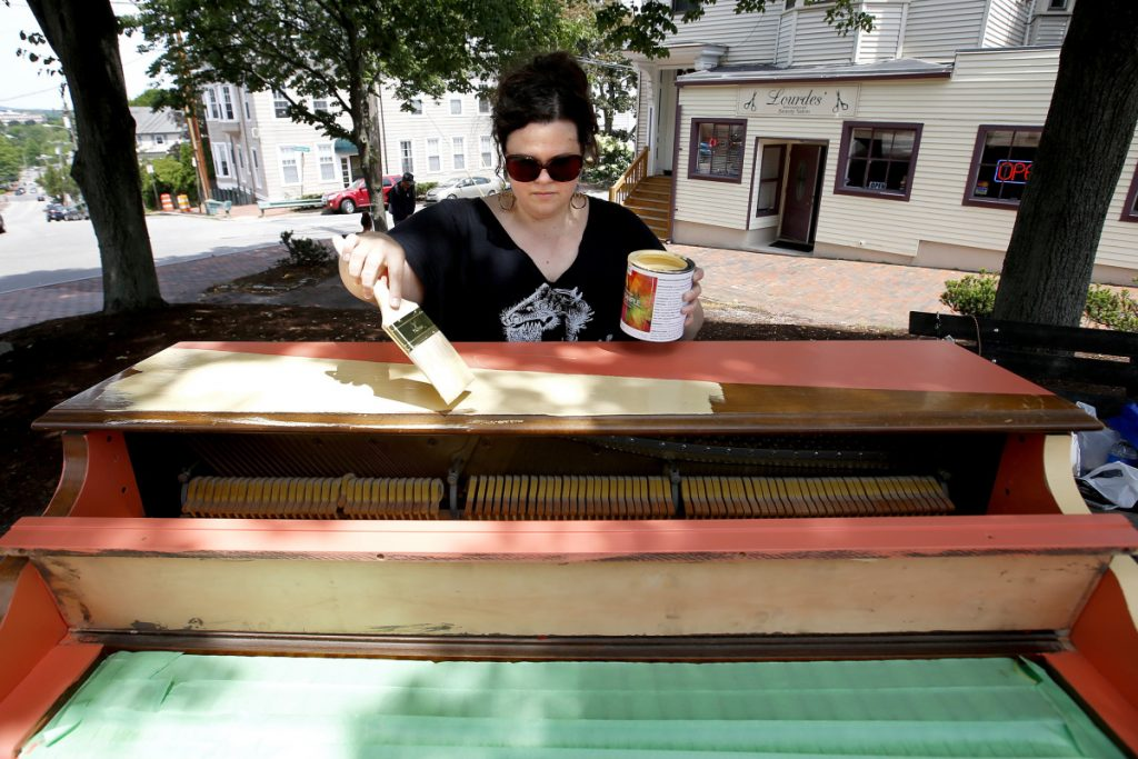 Adria Moynihan Rusk, founder of Still Life Studio, paints an upright piano on Wednesday in Bramhall Park, where it will eventually be displayed.